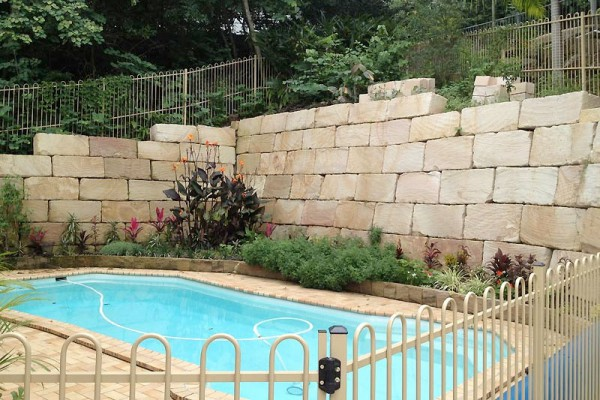 sandstone retaining wall around pool
